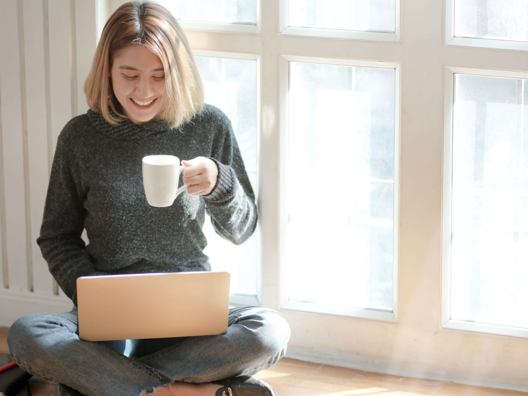 woman drinking coffee looking at computer